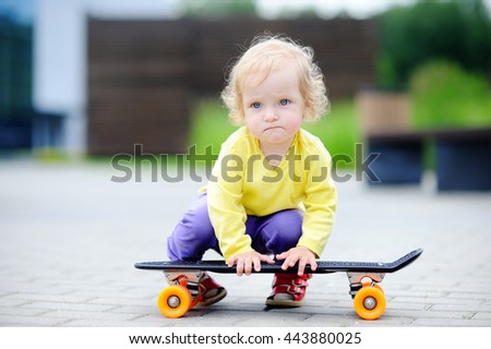 Cute toddler girl with skateboard outdoors  - stock photo