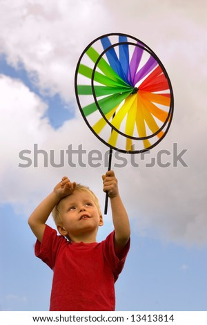 Cute toddler holds toy windmill up to the sky. - stock photo