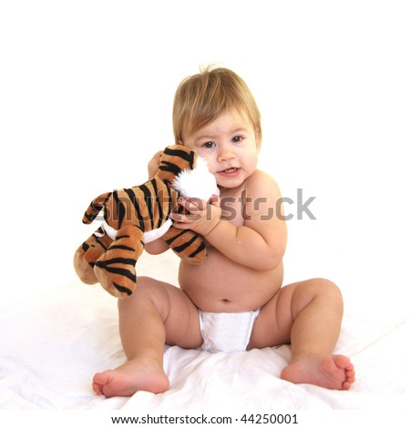 Cute toddler hugging tiger toy - stock photo