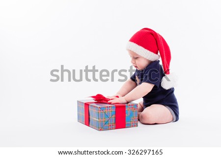 cute toddler is sitting in a New Year's red cap on white background unpacks a gift with a smile on his face, picture with depth of field - stock photo
