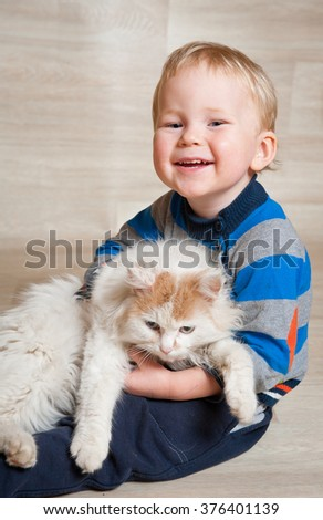 Cute toddler Kid baby boy playing with pet cat on the floor at home