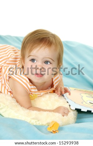 Cute toddler lying on her stuffed animal with a book - stock photo