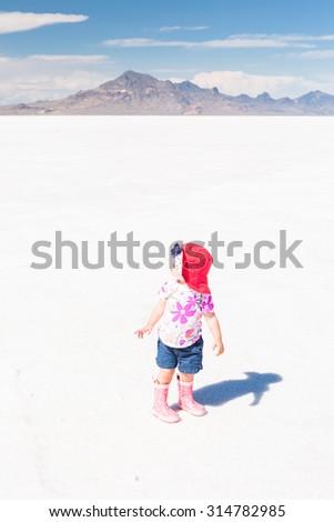 Cute toddler playing at Bonneville Salt Flats. - stock photo