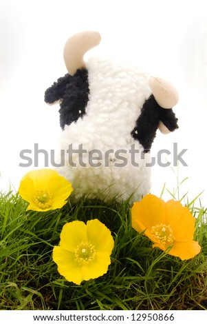 Cute Toy Cow in Grass and Flowers - stock photo