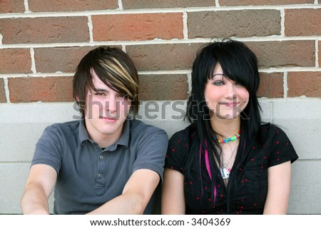 cute trendy male and female teens sitting outside - stock photo