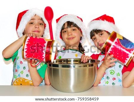 Cute triplet girls wearing Santa hats and aprons showing off at a kitchen counter with large metal mixing bowl and festive red jars. Isolated on white. Selective focus