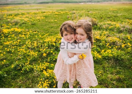 cute twin sisters, embrace on a background field with yellow flowers - stock photo