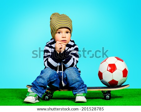 Cute two year boy sitting on a skateboard with a ball. Fashion. Childhood. - stock photo