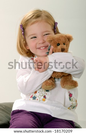 cute two year old blonde toddler poses with teddy - stock photo