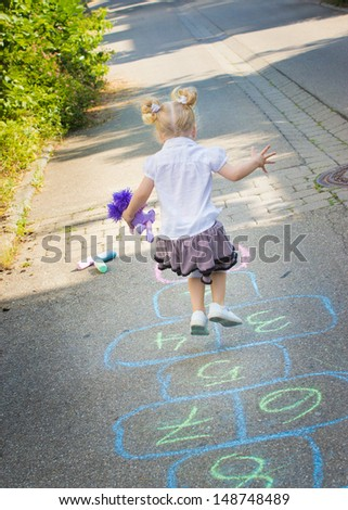 Cute two years old girl playing hopscotch on the street - stock photo