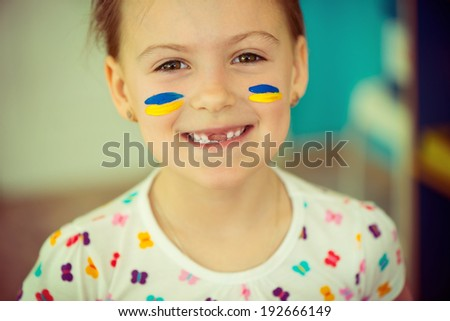 Cute ukrainian girl smiling with national flag on cheek - stock photo