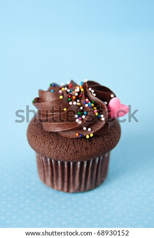Cute Valentine's Day Cupcake with Chocolate Icing and Colorful Sprinkles on Blue Background
