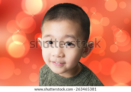 Cute Vietnamese boy looking and smiling against nice red background - stock photo
