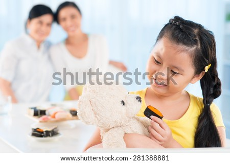 Cute Vietnamese girl feeding her teddy bear with sushi - stock photo