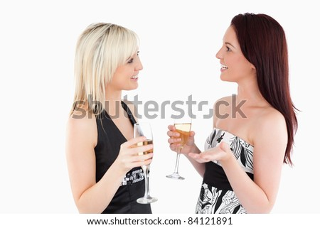 Cute well-dressed women drinking champagne in a studio
