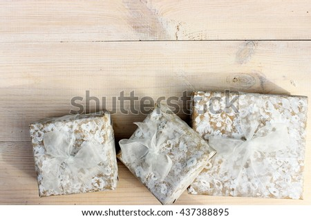 Cute white gift boxes wrapped with simple craft paper and handmade decorate with white drawing pattern and decorated with white ribbon and bow om wooden background. Concept for weeding. Copy space - stock photo