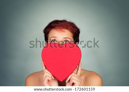 cute woman behind a red heart looking up - stock photo
