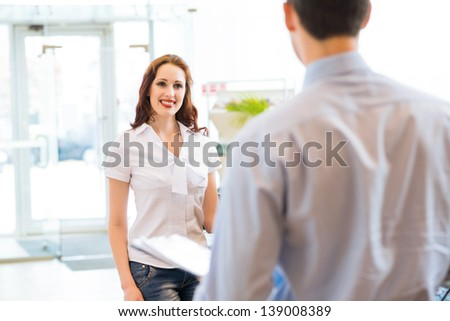 cute woman chooses a new car in the lounge car sales - stock photo