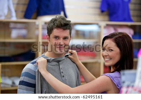Cute woman choosing clothes for her boyfriend in a shop - stock photo