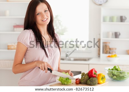 Cute woman cutting vegetables in a kitchen - stock photo