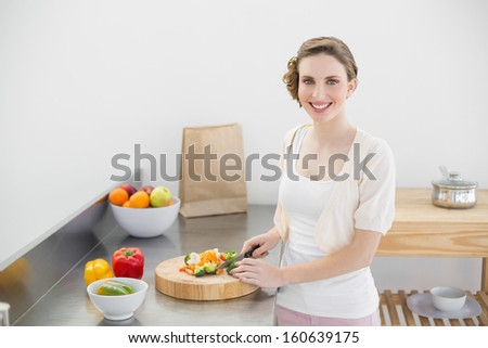 Cute woman cutting vegetables standing in her kitchen smiling at camera