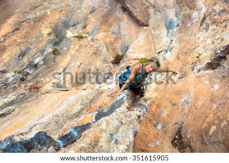 Cute Woman doing Exercise climb natural rock preparing for next Move Top View - stock photo