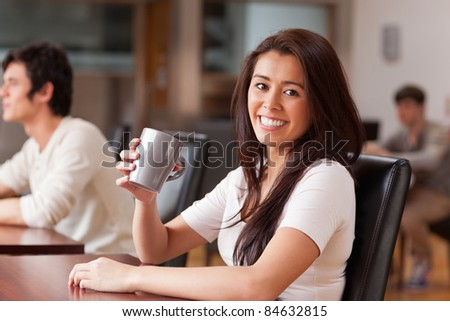 Cute woman having a coffee while looking at the camera - stock photo