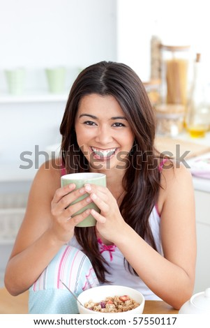 Cute woman holding a cup a coffee in the kitchen at home - stock photo