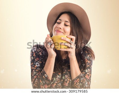 Cute woman holding a cup of coffee over ocher background