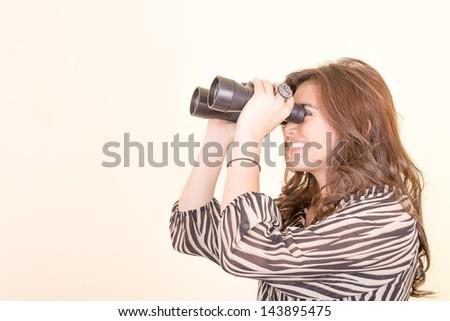 cute woman holding binoculars, yellow background - stock photo