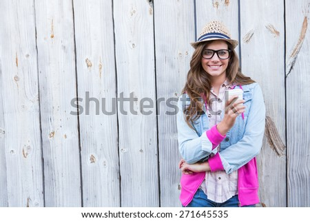 Cute woman holding disposable cup coffee against wooden planks
