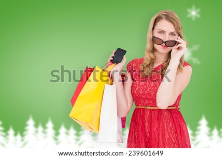 Cute woman holding shopping bags and her smartphone against blurred fir tree background