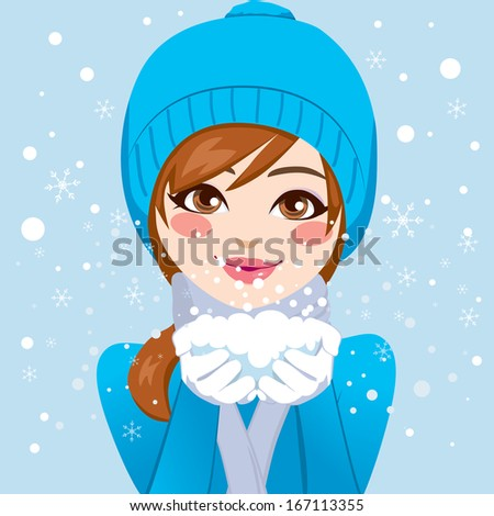 Cute woman in blue winter hat and warm clothing holding snow with hands close to her face blowing snowflakes softly - stock photo