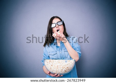 Cute woman in cinema glasses eating popcorn over gray background - stock photo