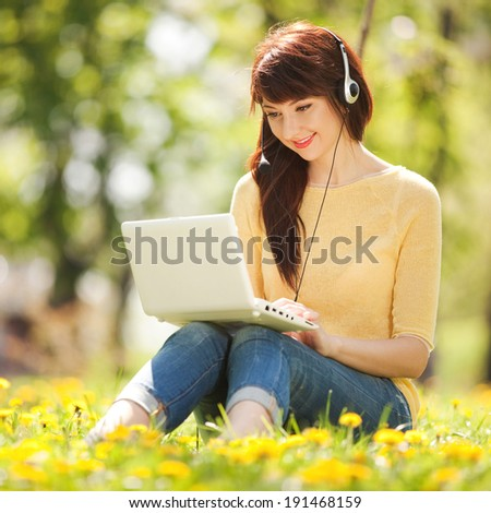 Cute woman in earphones with white laptop in the park - stock photo