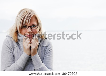 Cute woman in warm winter outfit protects from the cold. - stock photo