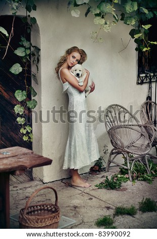 Cute woman in white dress hugging her puppy - stock photo
