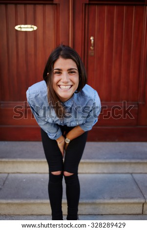 Cute woman is admiringly smiling, charming female model posing on the wooden door background. Fashionable street-look matches for trendy advertisement or your  message. Attractive hipster girl posing - stock photo
