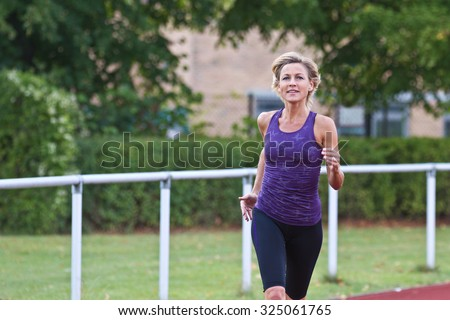Cute woman is sporty situation on a stadium - stock photo
