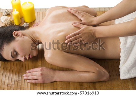 cute woman laying down on wood carpet with candle near getting an oil massage - stock photo