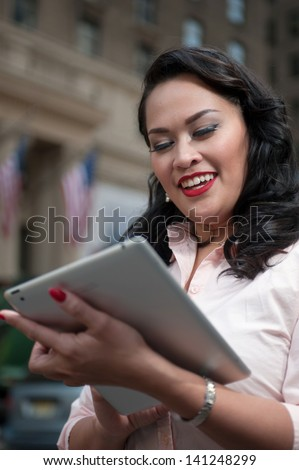 Cute woman on holiday in New York checks her tablet computer  - stock photo