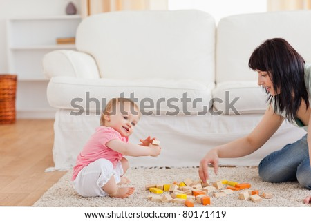 Cute woman playing with her baby in while sitting on a carpet in the living room - stock photo
