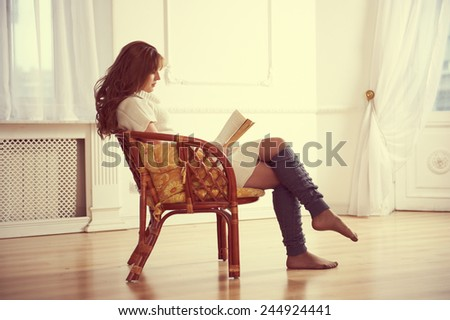 Cute woman reading a book in living room - stock photo