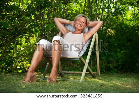 Cute woman relaxing on a deckchair outdoor in her  garden - stock photo
