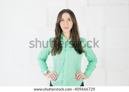 Cute woman standing and looking on white background. Smiling casual young businesswoman in green shirt and dark skirt on abstract background. - stock photo