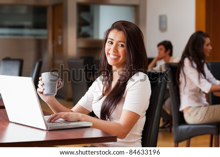 Cute woman using a laptop in a cafe - stock photo