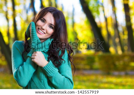 Cute woman wearing a turtleneck sweater in autumn park - stock photo