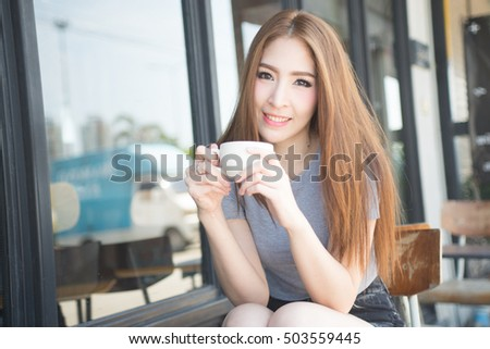 cute woman wearing gray T-shirt drink hot coffee on cafe place