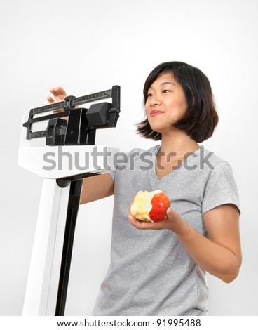 Cute woman weighing herself on weight scale and holding a red apple. Neutral white-gray background. - stock photo