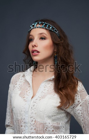 Cute woman with brown eyes wearing beaded headpiece and earrings